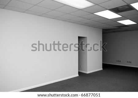 a large empty room with an opening and a drop ceiling in a vacant office building