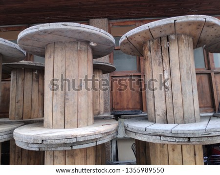 A large Empty Wooden Spools on a street.The spool is made out of pine wood. It has a light brown color. #1355989550