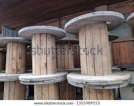 A large Empty Wooden Spools on a street.The spool is made out of pine wood. It has a light brown color. #1355989553