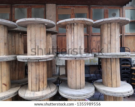 A large Empty Wooden Spools on a street.The spool is made out of pine wood. It has a light brown color. #1355989556