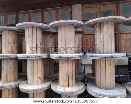 A large Empty Wooden Spools on a street.The spool is made out of pine wood. It has a light brown color. #1355989559