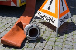 A large firefighters hose with a coupler lying on a cobbled street with a warning triangle with the German word for fire brigade (Feuerwehr)