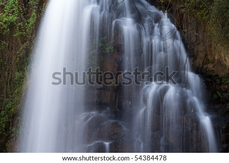 A large forest waterfall photographed with a slow shutter speed to create soft streaks of white water falling