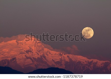 A large full moon rises above the snowy peak, glowing in red light because of the setting sun, of the mountain Himal Chuli in the nepali Himalayas. The picture was taken in Pokhara.