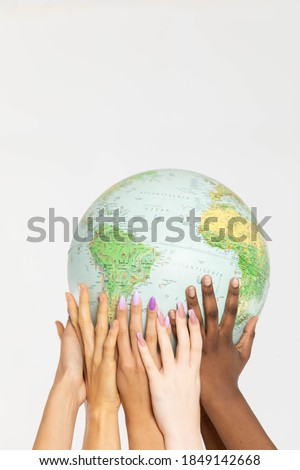 A large globe with all continents is supported by female hands of various races, symbolizing unity, acceptance and racial tolerance. Stock fotó ©