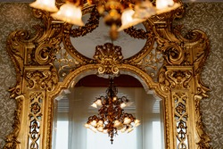 A large gold chandelier with patterns and many shades is reflected in a large antique wall mirror with a gilded carved frame.