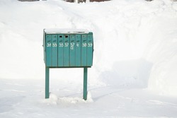 A large green mailbox with drawers and numbers written on them. Winter on the street.