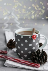 A large grey Cup of hot coffee drink with a Lollipop on a dark concrete background. Winter. Holiday concept, selective focus.