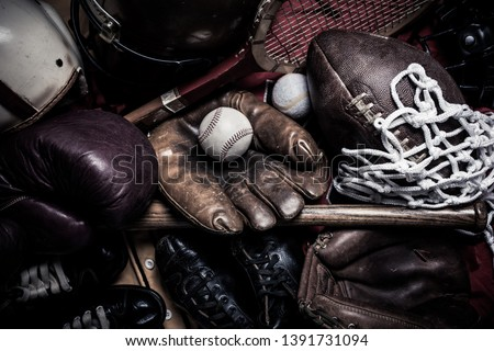 A large group of assorted vintage antique sports equipment. Including football helmet, baseball and boxing gloves etc. Stock photo ©