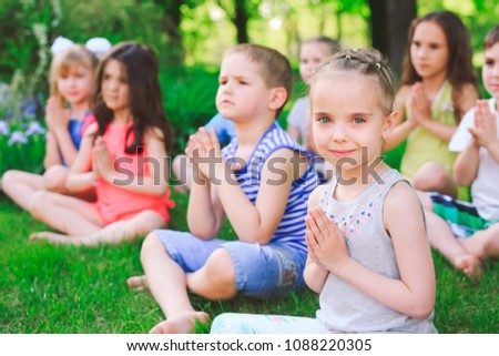 A large group of children engaged in yoga in the Park sitting on the grass. #1088220305