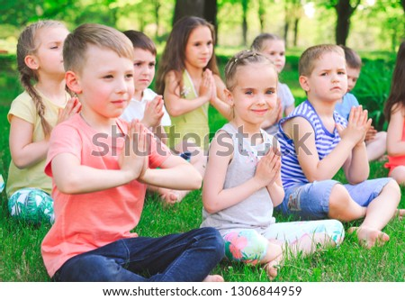 A large group of children engaged in yoga in the Park sitting on the grass. #1306844959