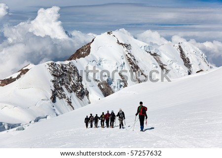 A large group of mountaneers walking on a glacier in a sunny day: in background the snowed peaks of Lyskamm (4550 mt) , Monte Rosa range, West Alps, Switzerland, Europe.