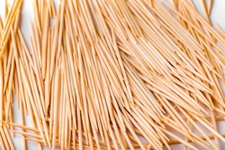 A large group of pointed, sharp toothpicks made of wood close-up. Texture, pattern, and background of toothpicks.