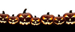A large group of seven spooky halloween lanterns, Jack O Lantern, with evil face and eyes isolated against a white background.