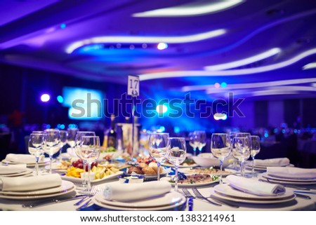a large hall with laid tables awaits guests