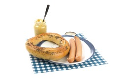 a large Hamburg pretzel and two Vienna sausages on a blue plate and a jar of Parisian mustard isolated on white