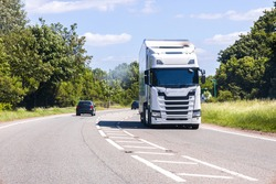A large HGV vehicle traveling along one of the main road routes of the United Kingdom, on a summer's day. Taking goods to and from their suppliers and customers.