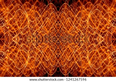 A large horizontal shot is a symmetrical light pattern of an orange light trail on a black background in the form of thin curved intersecting curves, long exposure. #1241267596