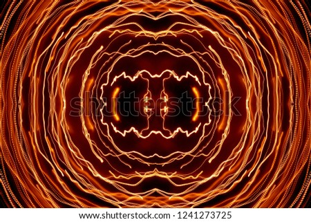 A large horizontal shot is a symmetrical light pattern of an orange light trail on a black background in the form of thin curved intersecting curves, long exposure. #1241273725