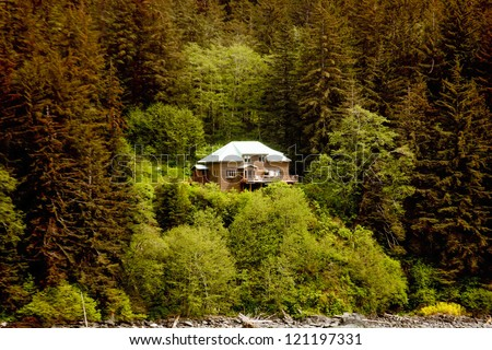 A large house perched on the side of a fir covered hill in the wilderness of Alaska - stock photo