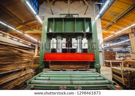 A large hydraulic press in the shop in the middle of the wood blanks presses the wood layers for the production of plywood. Workshop for the production of particle boards.  Wood processing. Foto d'archivio ©