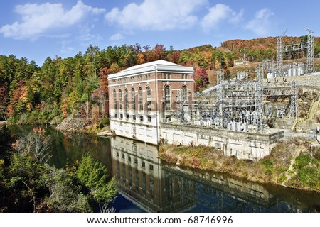 A large hydroelectric power plant on a river with the autumn colors around it.