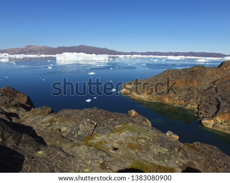 A large iceberg and many small icebergs drift and melt in a fjord in northwest Greenland #1383080900