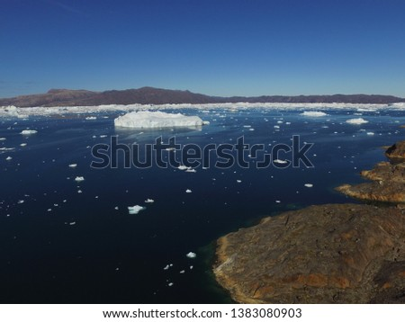 A large iceberg and many small icebergs drift and melt in a fjord in northwest Greenland #1383080903