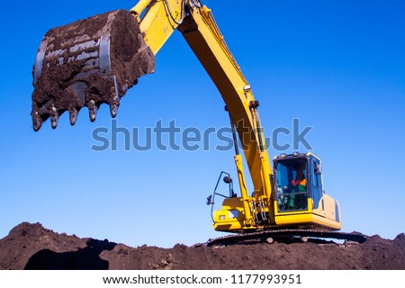 A large iron excavator bucket collects and pours sand rubble and stones in a quarry at the construction site of road facilities and houses