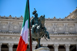 A large Italian national flag next to the equestrian statue of King Vittorio Emanuele II in the center of Rome