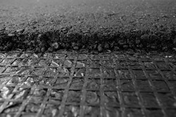 A large layer of fresh hot asphalt. Layer of asphalt raw material in a shallow dept of field.