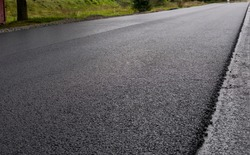 A large layer of fresh hot asphalt. Layer of asphalt raw material in a shallow depth of field. Rollers rollin fresh hot asphalt on the new road. Road construction. Construction of a new road.