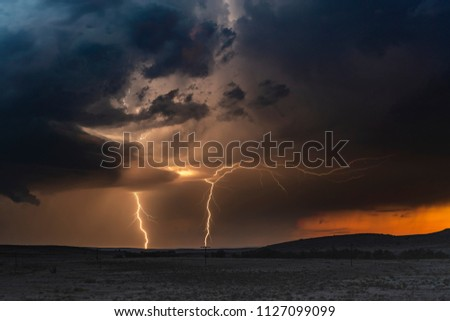 Stock Photo A large lightning strike at dusk in an open plain framed against a deep, dark orange sunset and stormy skies.