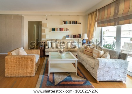 A large living room warm contemporary style with two sofas of two seaters, one straw sofa, lamps, coffee table, carpet and stands on the wall with books. The floor is oak wood. #1010219236