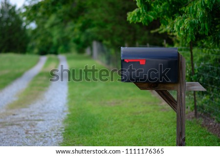 A large mailbox with the flag down along a gravel road.