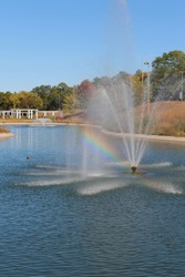 A large, manmade pond with a water fountain and a rainbow in the water spray in the midst of Sinnissippi Gardens in Rockford, Illinois, USA