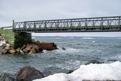 A large metal footbridge spans over a river near the ocean.  The background is a cloudy sky with some blue breaking through.  The bailey bridge has a metal structure with a wooden deck and cribbing.