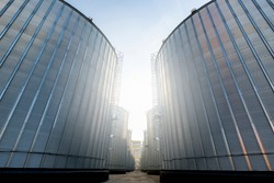 A large modern plant for the storage and processing of grain crops. view of the granary on a sunny day. Large iron barrels of grain. silver silos on agro manufacturing plant for processing and drying