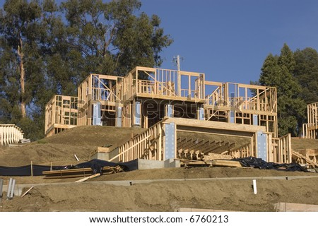 Large modern wood framed house under construction with carpenters