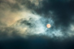 A large moon in a cloudy sky with thick clouds. Full moon. The night sky with the bright light of the full moon.Clouds at night time