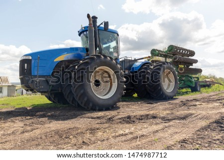 A large, multi-wheeled, blue tractor stands in a field with a green disc plow.A large, multi-wheeled, blue tractor stands in a field with a green disc plow.