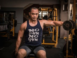 A large muscular asian man does seated one arm dumbbell side raises with both arms. Shoulder workout at a hardcore gym.