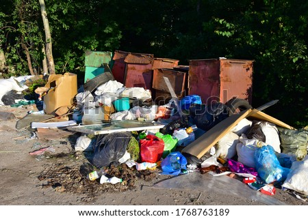 A large number of accumulated plastic bags and plastic packaging of household waste in garbage containers. The problem of garbage removal from the village, the concept of environmental pollution Сток-фото ©