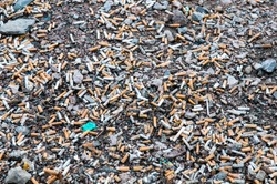 A large number of cigarette fag end on the ground in front of the station