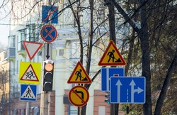 a large number of road signs, symbols of detours, road repairs near the traffic light with a pedestrian crossing on the background of city buildings and tree branches