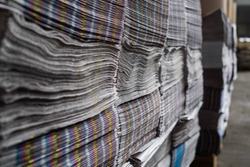 A large number of the issued newspapers in the printing house shop. A heap of multi-colored newspapers lie the friend on the friend. Production shop