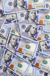 A large number of US dollar bills of a new design with a blue stripe in the middle. Top view