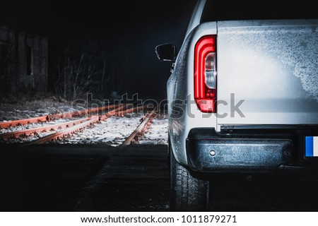 A large off-road white pickup truck. A view of the off-road car at night on the railway tracks. View of the back of the car, in front of the car, a railway crossing.