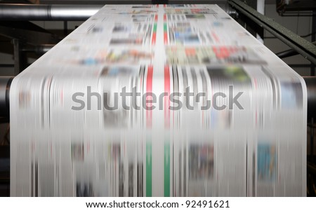 A large offset printing press running a long roll off paper over its rollers at high speed. Stock photo ©