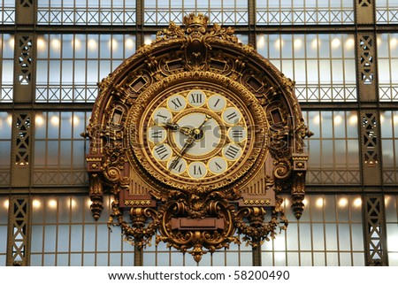 A large old decorated antique clock at an old train station. The clock face has Roman numerals.